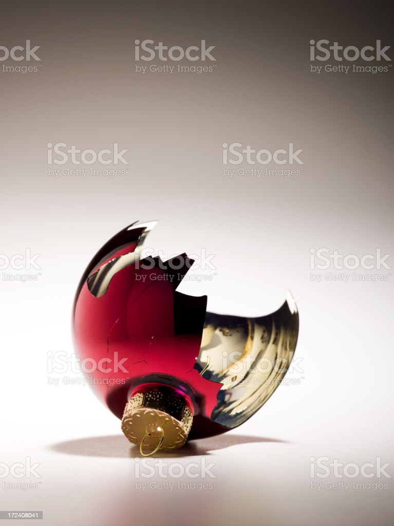 Broken red Christmas ornament on white backdrop royalty-free stock photo