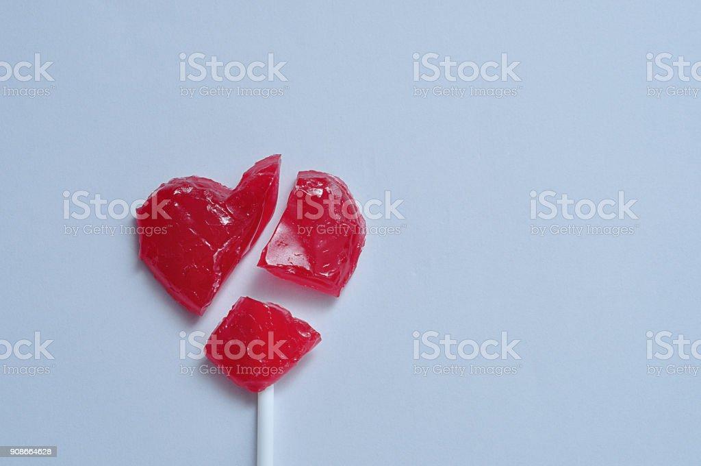 A broken red heart lollipop symbolizing a broken heart stock photo