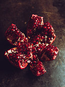 Broken red ripe pomegranate fruit on the dark rustic background. Selective focus. Shallow depth of field.