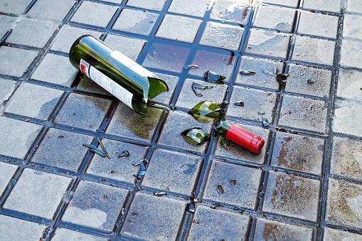 broken red wine bottle on the floor