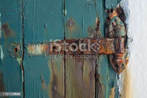 A broken rusting door hinge on a painted wooden door, paint peeling off the wood, nobody in the image