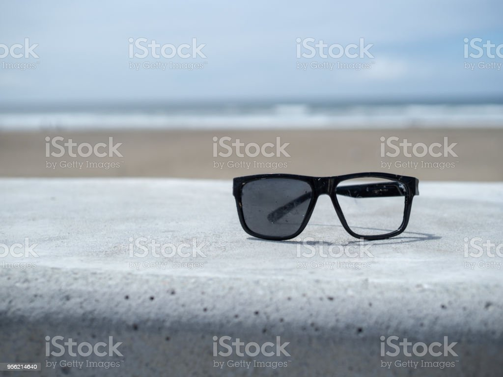 Broken set of sunglasses sitting on a concrete wall overlooking beach stock photo