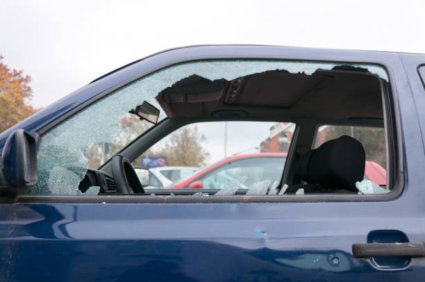 Broken side window glass on the damaged car door stock photo