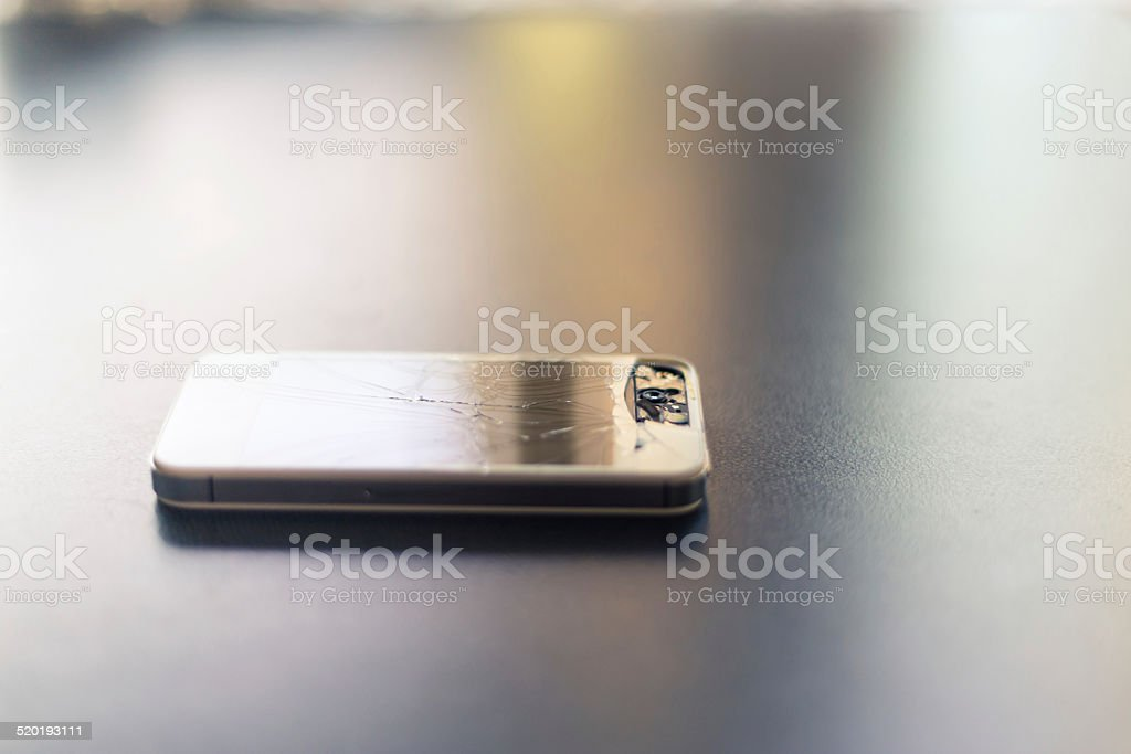 Broken smart phone on a table top stock photo