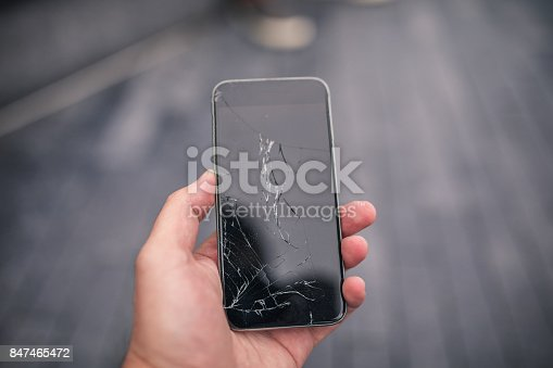 Man holding a broken smart phone in his hand, part of.