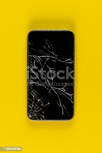 Broken smart phone on the yellow paper background.