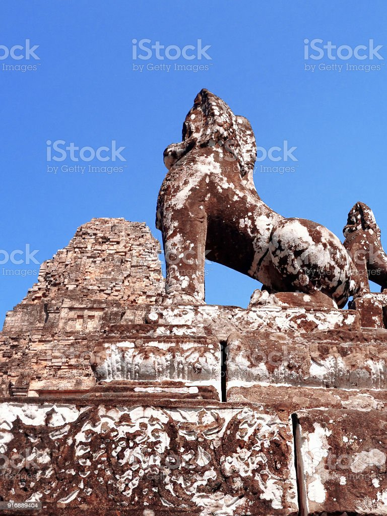 Broken statues of lions at the ruins of Ta Keo temple in Siem Reap Cambodia. This archaeological site is of significant historical importance to the Hindu and Buddhist religions. stock photo