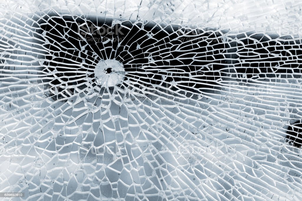 Broken strained glass with bullet hole and craks. Close-up background...