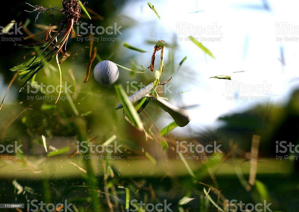 Broken Tee with Golf Ball in Flight stock photo
