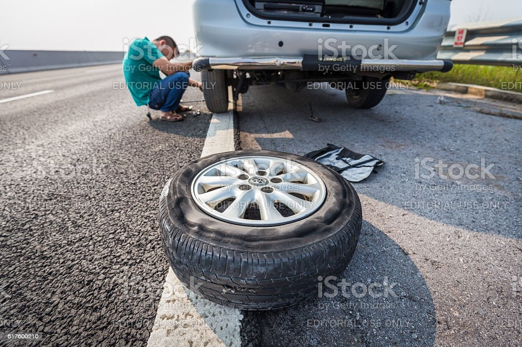 Broken tire with background of driver fixing wheel stock photo