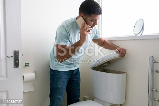 A side-view shot of a man standing in his bathroom looking at his toilet, there is a problem, he is on the phone trying to call a plumber.