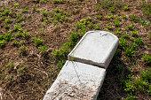 Broken Tombstone on the Ground - Stock Photo