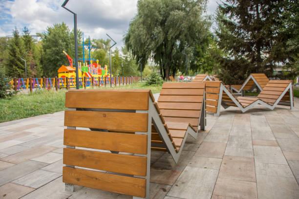 verdrehte holzbänke als eine option urban straßendekoration auf bunten spielplatz hintergrund gebrochen. damm in der nähe des flusses desenka in kiew ukraine - spielplatz design stock-fotos und bilder