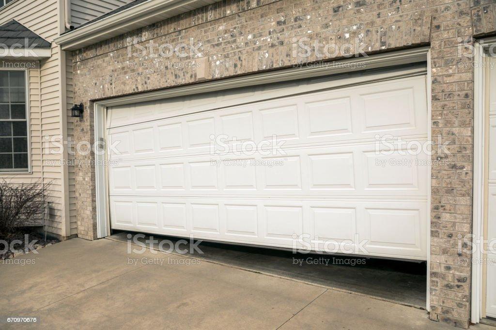 Broken Two Car Garage Door in Residential Home stock photo