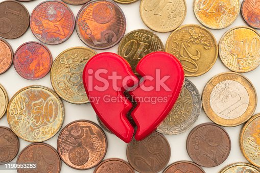 istock Broken Valentine's Day heart on a pile of euro coins. 1190553283