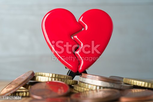 istock Broken Valentine's Day heart on a pile of euro coins. 1191213634