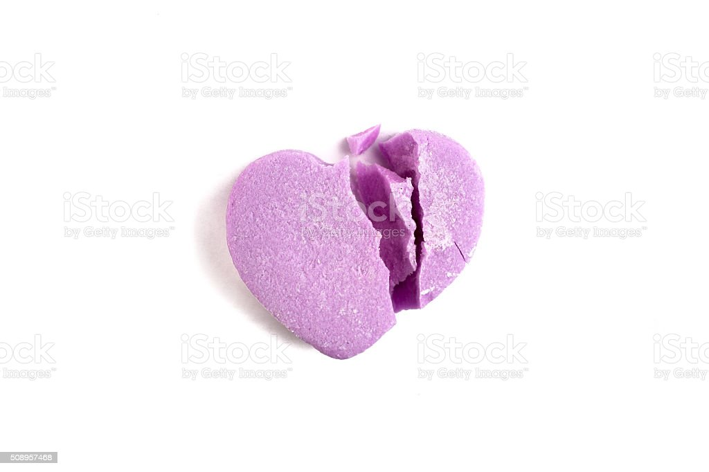 Broken Valentine's Day purple candy heart on white background stock photo