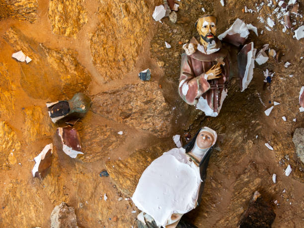 Broken vandalized plaster catholic plaster statues in the ground stock photo
