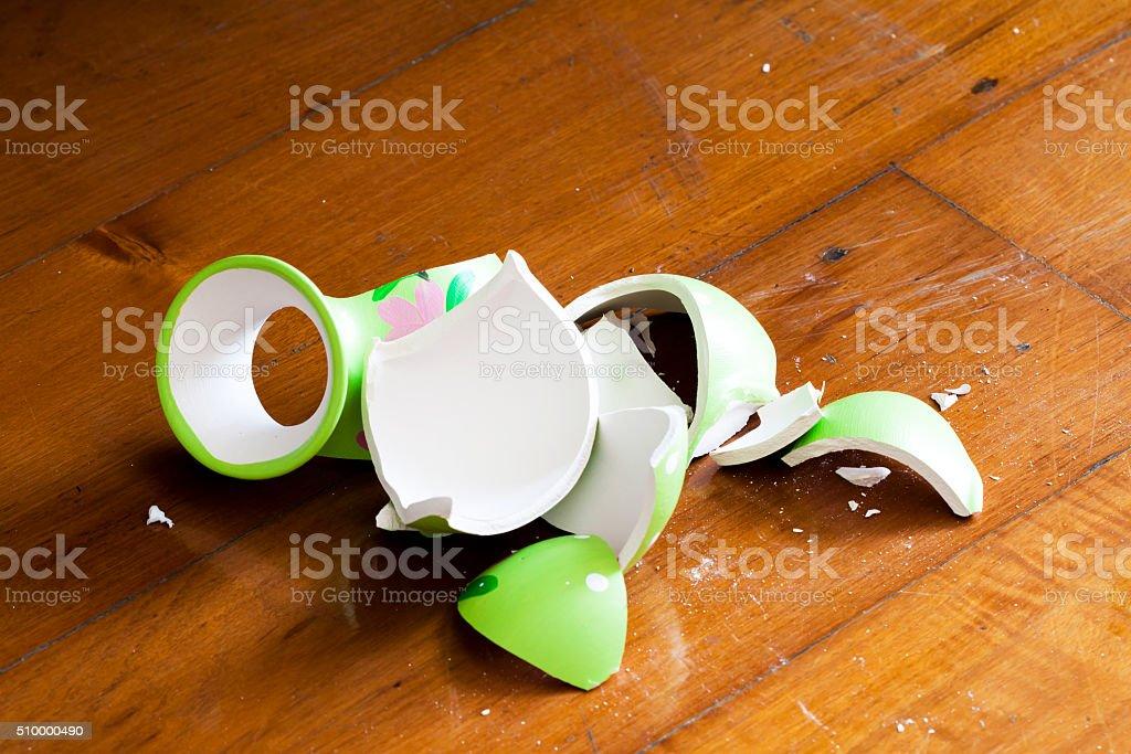 broken vase on wooden floor stock photo