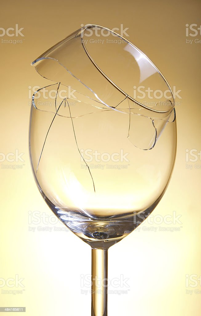 Broken vine glass on orange background stock photo