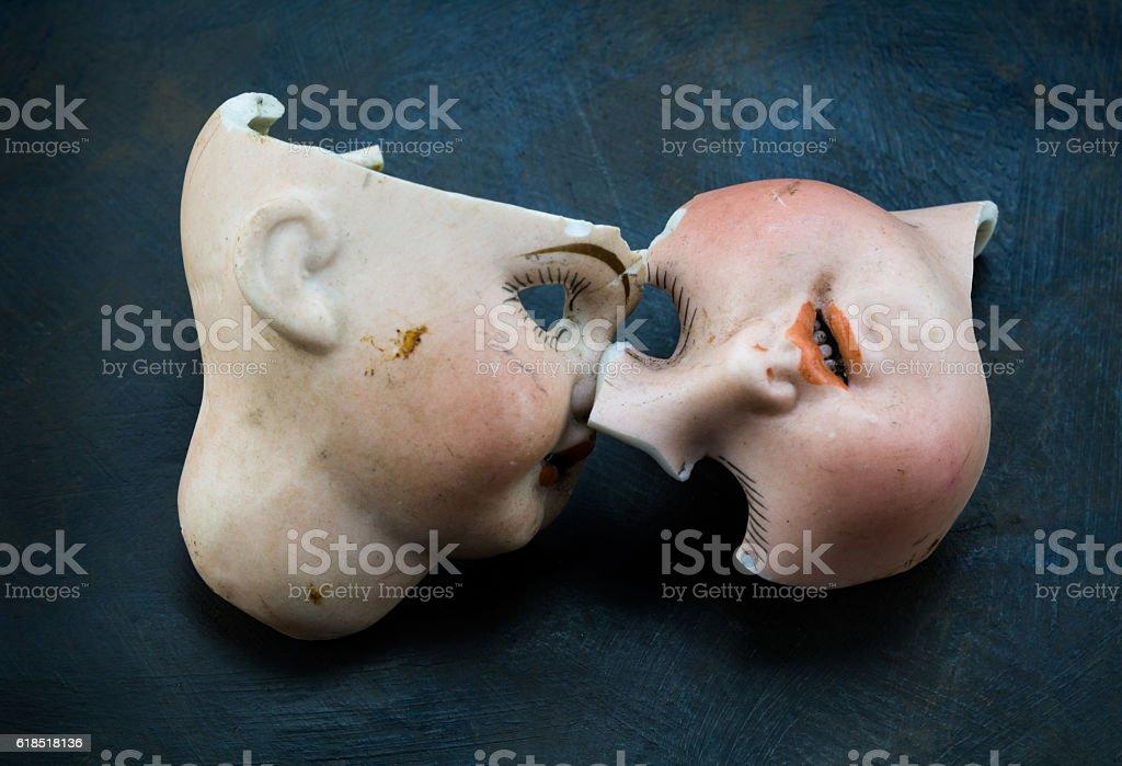 Broken vintage doll face parts on grunge background