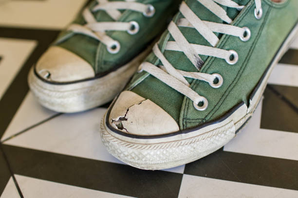 Broken vintage sneakers on pattern background Broken vintage sneakers on black and white background all star stock pictures, royalty-free photos & images
