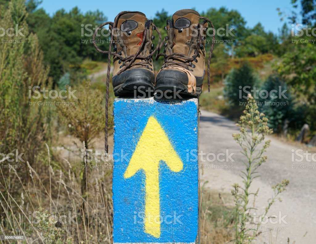 Broken walking shoes on the top of a waymark along the Way of St. James, Spain, Europe stock photo