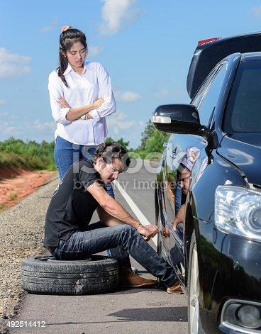 104275470istockphoto Broken wheel man changing tire help female friends 492514412