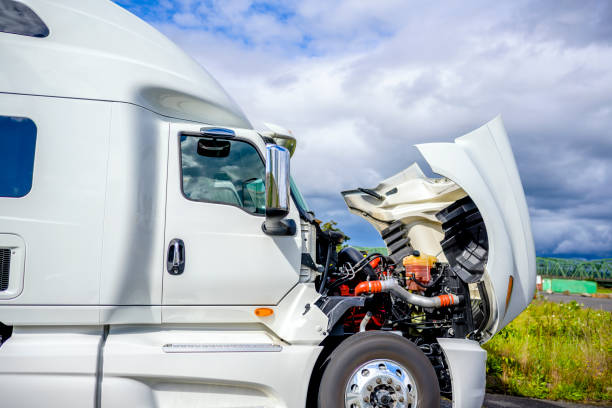 Broken white big rig semi truck tractor stands on the side of the road with an open hood awaiting mobile repair assistance stock photo