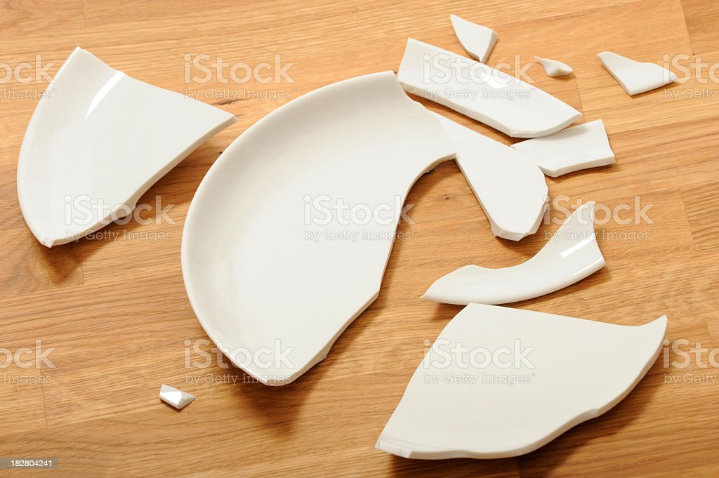 A broken white ceramic plate on a wooden floor stock photo