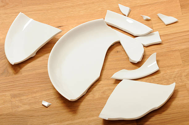 a broken white ceramic plate on a wooden floor - gebroken bord stockfoto's en -beelden