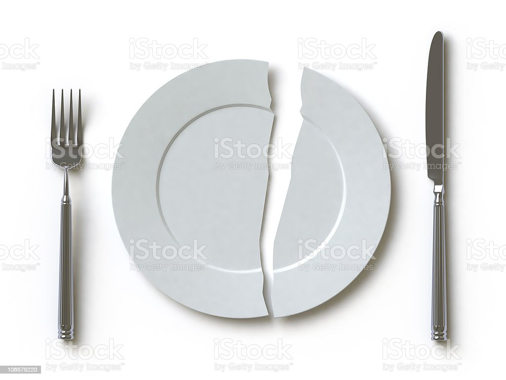 Broken white plate between a knife and fork stock photo
