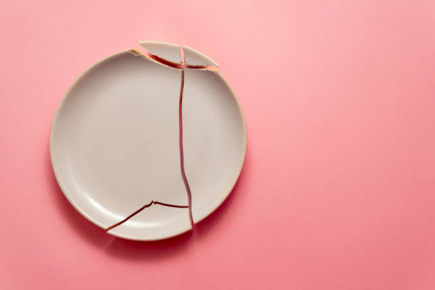 broken white plate on pink background, concept visual stock photo