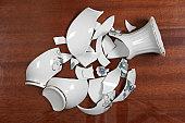 Broken white porcelain vase on wooden floor