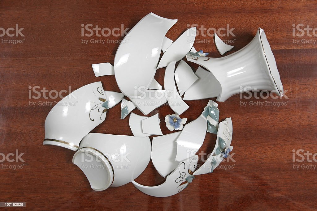 Broken white porcelain vase on wooden floor stock photo