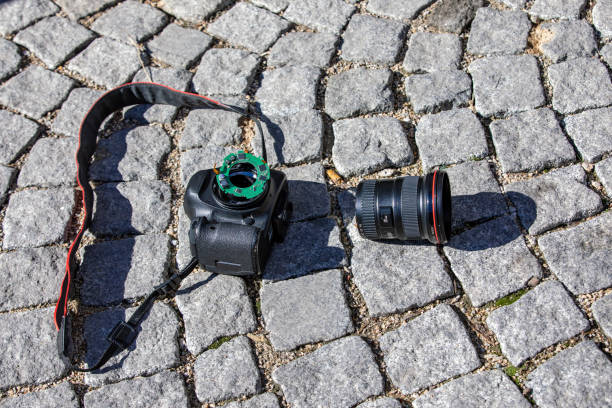 broken wide angle lens and digital camera stone block pavement stock photo