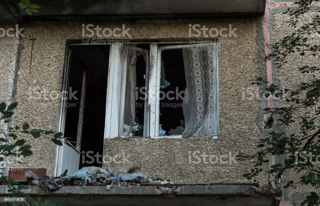 Broken window and balcony sawn in an abandoned apartment building. Debris devastation. stock photo