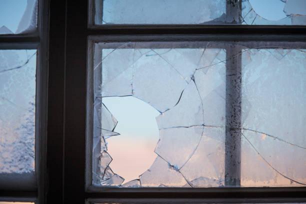 Broken window glass with a winter scenery outside. stock photo