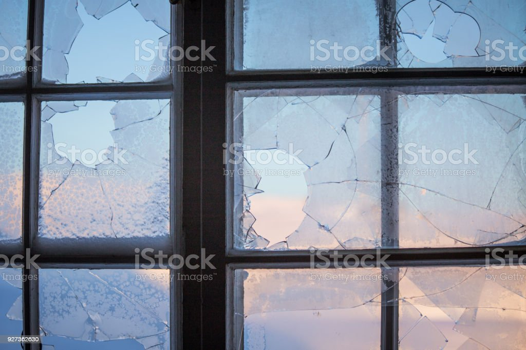 Broken window glass with a winter scenery outside. Broken window glass with a winter scenery outside. Ruined historic building with a shattered window. Beauty Stock Photo