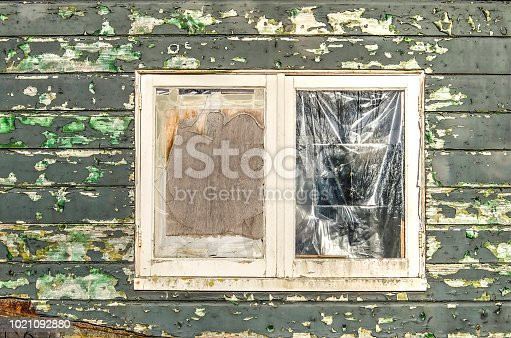 Window with broken glass, closed with plastic and plywood; in a wooden facade with peeling green paint
