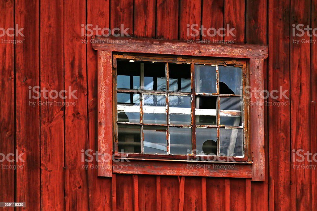 Broken window in red barn stock photo