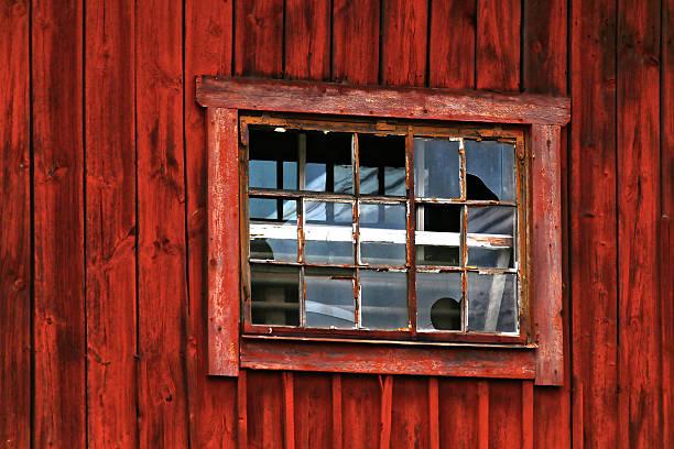 Broken window in red barn stock photo