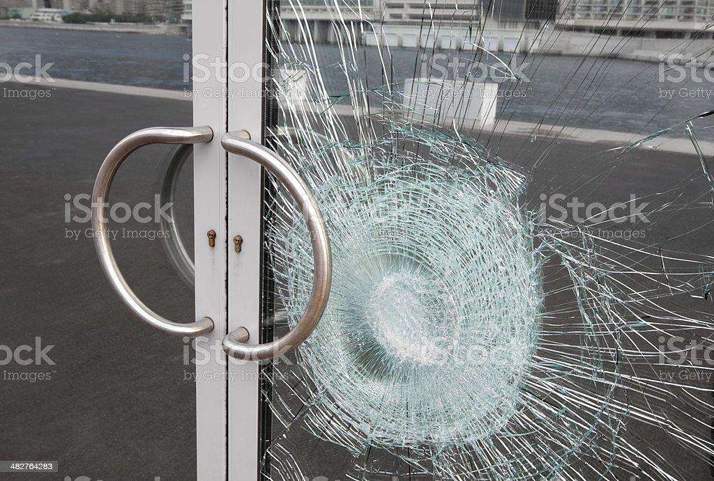 Broken window on business glass door shattered by vandalism Broken glass door panel with smashed area. Shattered window on business entrance of an office building facade cracked and damaged by vandalism. The doubled glass pane is silvered on the back reflecting the cracks and sidewalk. Door Stock Photo