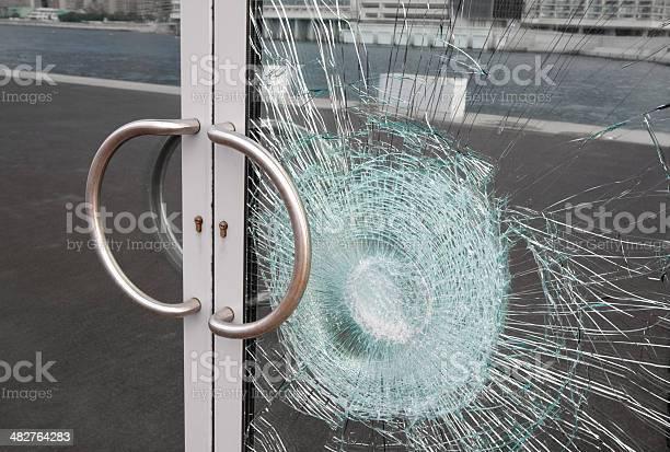 Broken Window On Business Glass Door Shattered By Vandalism Stock Photo - Download Image Now