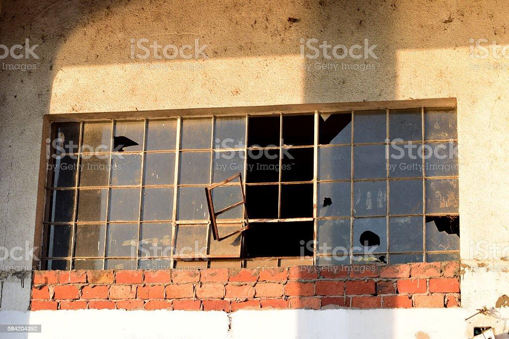 Broken window on the old building stock photo