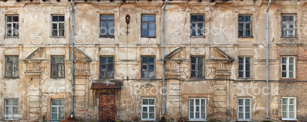 Broken windows and  wall in an old non residential no name house  that was built over a hundred years ago. stock photo