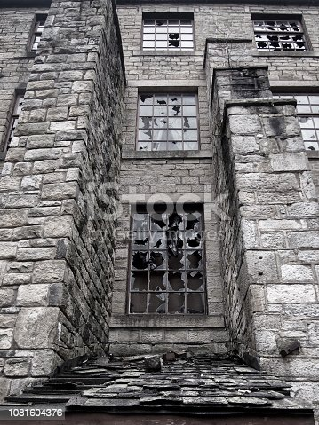 broken windows in an empty abandoned vandalized old stone building