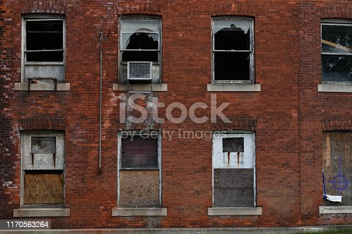 Broken and boarded-up windows of abandoned factory