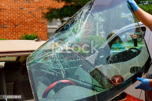 Broken windshield car special workers take of windshield of a car in auto service from inside from accident of car.