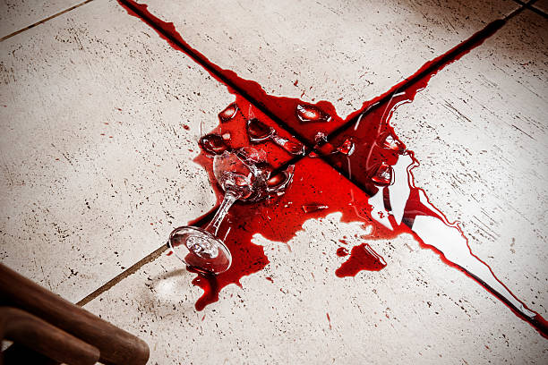 Broken wine glass and red wine on the floor stock photo